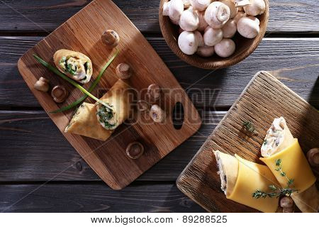 Pancakes with creamy mushrooms on wooden table, top view