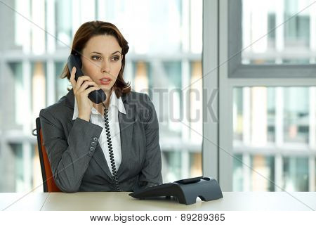 portrait of young confident caucasian businesswoman talking on phone