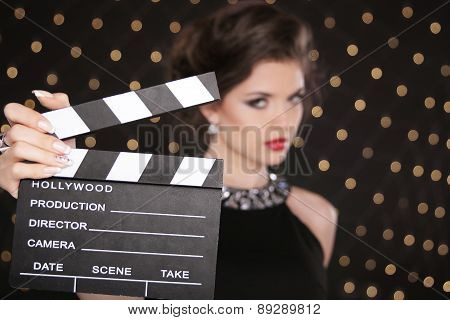 Hand Holding Cinema Clap Against The Fashion Woman With Sexy Red Lips Around Light Background. Super