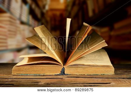 Old book on wooden table on bookshelves background
