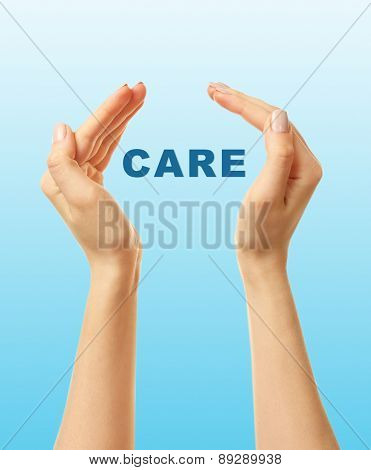 Female hands with word care on blue background