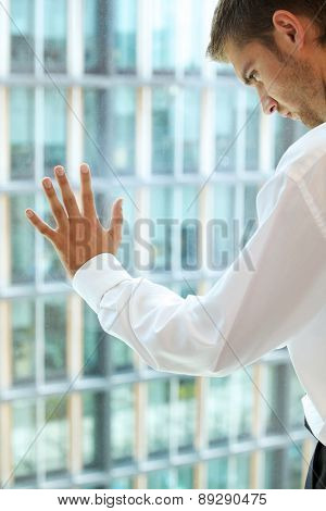 Young caucassian businessman standing against office window