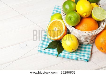 Citrus fruits in basket. Oranges, limes and lemons. Over wooden table background with copy space