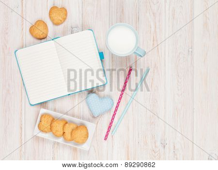 Notepad, cup of milk, heart shaped cookies and gift toy on white wooden table