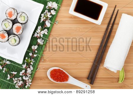 Sushi maki set with fresh sakura branch over bamboo table with copy space