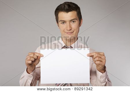 Young happy businessman with good sales results document in his hands