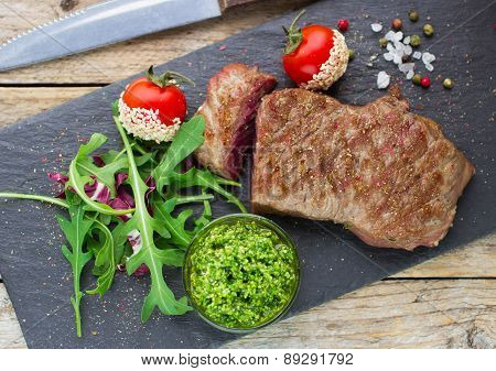 Beef Steak Grilled With Tomatoes, Arugula And Pesto On Black Plate