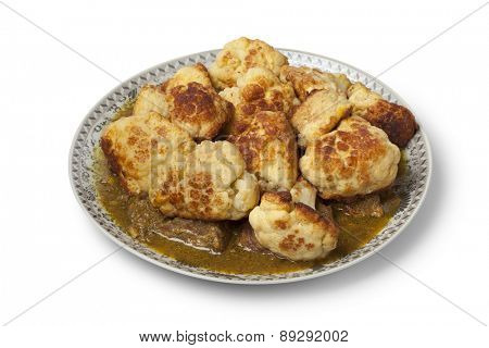 Moroccan traditional deep fried cauliflower with beef and sauce on a dish on white background
