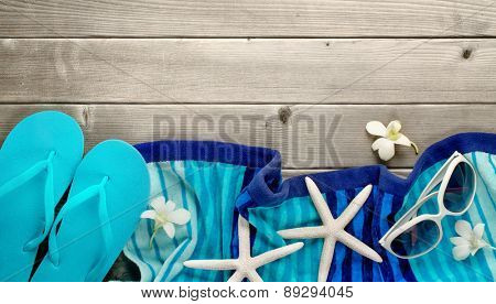 Towel and beach slippers on wood background