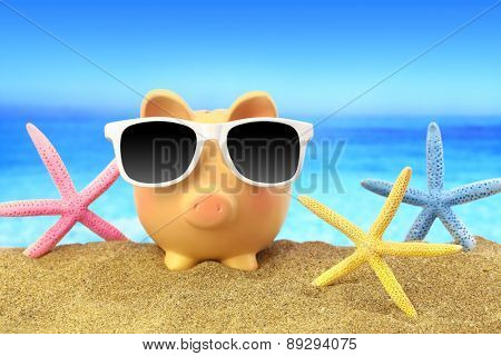 Summer piggy bank with sunglasses and starfishes on beach