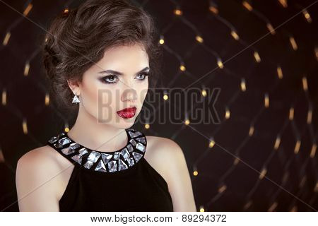 Beautiful Brunette Woman Model With Makeup And Hairstyle In Fashion Earrings Over Bokeh Lights Backg