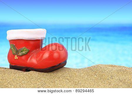 Santa claus boot ornament on sandy beach