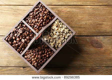 Coffee beans in box on wooden table, top view