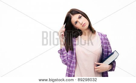 Thoughtful young female student standing with book over white background and looking at camera