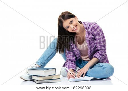 Happy woman sitting on the floor and writing in notebook over white background. Looking at camera