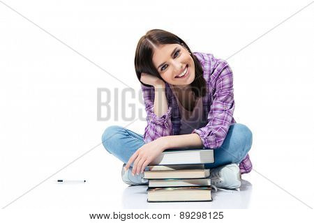 Happy woman sitting on the floor with books over white background and looking at camera