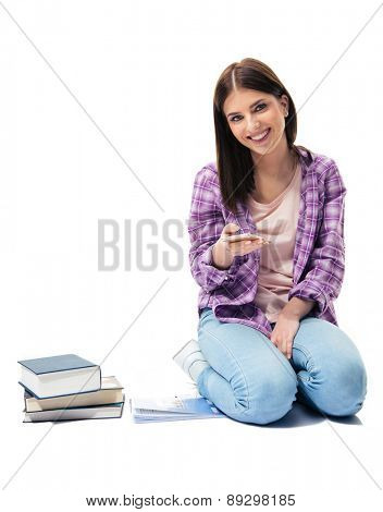 Smiling young girl sitting on the floor with smartphone and books over white background. Looking at camera