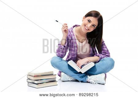 Smiling woman sitting on the floor with books over white background and looking at camera