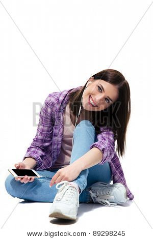 Happy young girl sitting on the floor with smartphone and headphones over white background and looking at camera