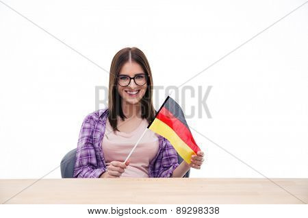 Young woman sitting at the table and holding German flag over white background. Looking at camera
