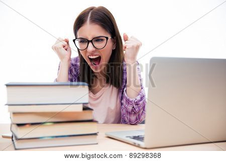 Angry woman sitting at the table with books and laptop over white background. Screaming