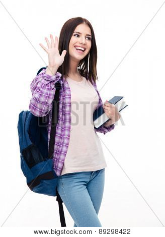 Happy young woman with backpack and book making greeting gesture with palm over white background. Looking away