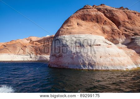 Picturesque artificial huge reservoir Powell on the river Colorado, USA. The lake is surrounded with amazing coast from orange sandstone. Walk by tourist motor ship on water on a sunset