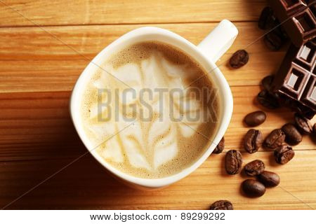 Cup of coffee latte art with grains and chocolate on wooden table, closeup