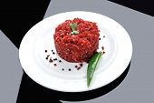foto of hamburger-steak  - very big raw hamburger cutlet with sprouts and chilli pepper on white plate over black background - JPG