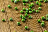 picture of sweet pea  - Organic frozen baby sweet peas on wood board - JPG