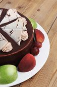 stock photo of cream cake  - chocolate cream brownie cake topped with white chocolate slice and cream flowers decorated with fruits apple plum and grape on plate on wooden table - JPG