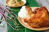picture of thighs  - Deep fried Chicken thigh with sticky rice on wooden plate - JPG