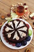 picture of cream cake  - big whole frost chocolate cream brownie cake topped with white chocolate and cream flowers with hot tea cup decorated with fruits apple plum and grape on plate on wooden table - JPG