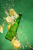 stock photo of freezing  - Green beer bottle with splashing liquid - JPG