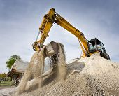 picture of excavator  - Excavator standing on top of gravel hill and moving gravel with scoop - JPG