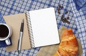 image of croissant  - Notepad with empty page croissant and coffee cup on blue tablecloth top view - JPG