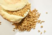 stock photo of flat-bread  - Wheat grains placed over baked flat bread on white background - JPG