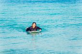 image of board-walk  - A young surfer with his board on the beach - JPG