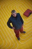 image of convection  - group of workera installing underfloor heating and colling in modern home - JPG