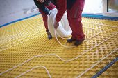 image of convection  - grouo of workera installing underfloor heating and colling in modern home - JPG