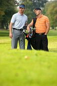 foto of golf bag  - Young men standing on golf course carrying bags - JPG