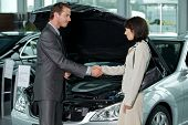 stock photo of showrooms  - Car salesperson shaking hands with customer at showroom - JPG