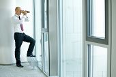 stock photo of inquisition  - caucasian businessman spying using telescope thru office window - JPG