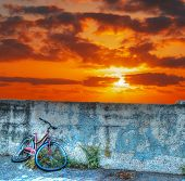 image of wrecking  - old bike wreck against the wall at sunset - JPG