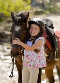 picture of year horse  - sweet beautiful young girl 7 or 8 years old hugging head of little pony horse smiling happy wearing safety jockey helmet posing outdoors on countryside in summer holiday - JPG