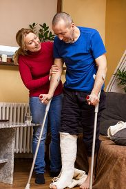stock photo of crutch  - A man with broken leg taking its first steps with crutches - JPG