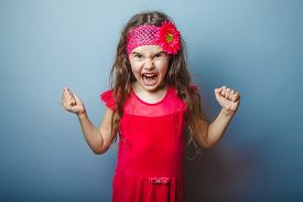 stock photo of shout  - Girl European appearance haired child of seven in red bright dress on a gray background shouts - JPG
