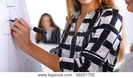 Young woman with folder writing on board