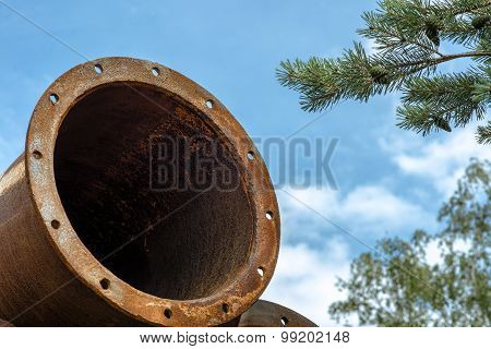 Rusted industrial steel pipes on the tree and blue sky background.