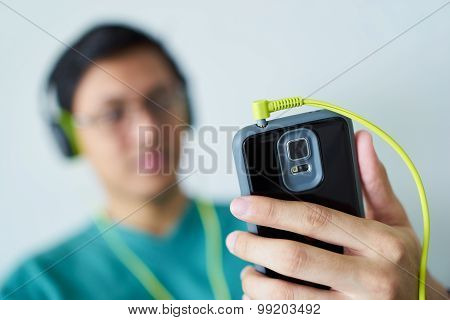 Chinese Man With Green Headphones Listens Music Podcast Phone